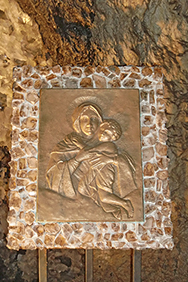 Marienbild mit Rahmen aus Marienglas, das die Farbe des Bronzereliefs angenommen hat.