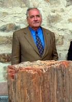 Reinhard Balzer hinter dem versteinerten Baumstamm aus Arizona